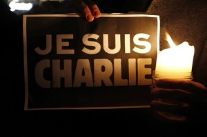 "A person holds a candle in front a placard which reads ""I am Charlie"" to pay tribute during a gathering in Strasbourg"