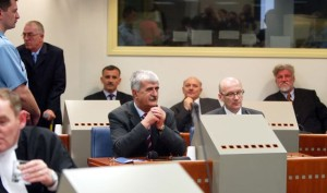 THE HAGUE, NETHERLANDS - APRIL 6: Bosnian Croats (back row L-R) Berislav Pusic (standing), Valentin Coric,  General Milivoj Petkovic, General Slobodan Praljak and front row (L-R) Bruno Stojic and former Foreign Minister of Bosnia Herzegovina Jadranko Prlic make their initial appearance April 6, 2004 at the War Crimes Tribunal in The Hague, Netherlands. The group of six Bosnian-Croats, who surrendered themselves, have been indicted for war crimes against Bosnian Muslims in the 1990's. (Photo by Michel Porro/Getty Images)